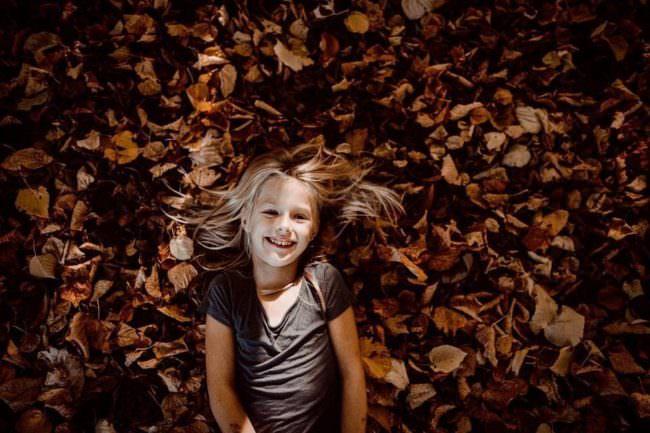 Kind liegt im Laub