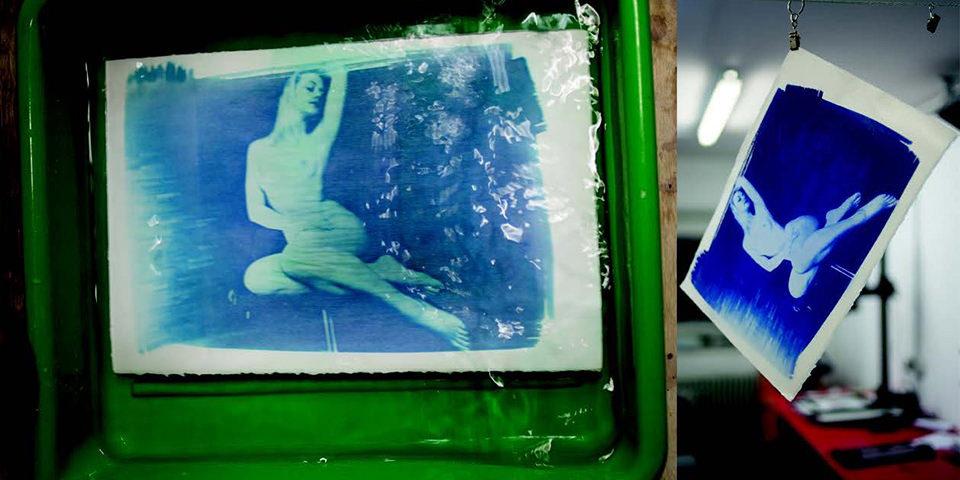 Bild einer Frau im Akt in blau in einer Entwicklerwanne und an einer Trockenleine.