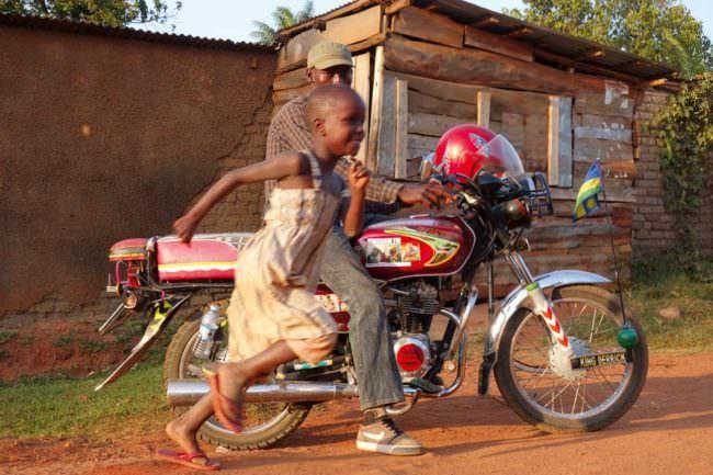 Ein Kind rennt neben einem Motorrad