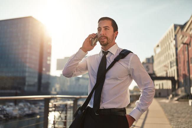 Junger dynamischer Business Gründer macht Termine am Smartphone