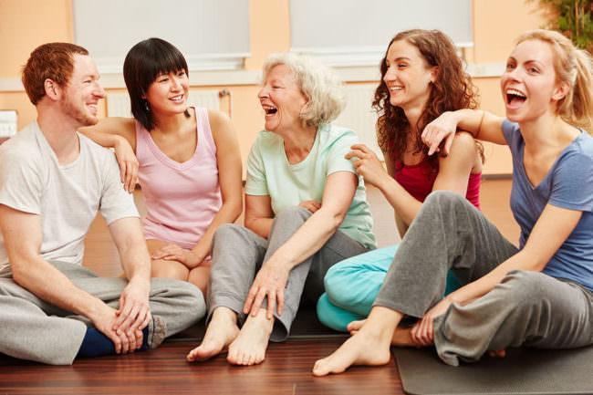 Vitale Seniorin und Gruppe lachen glücklich im Fitnesscenter