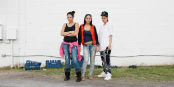 Drei Jugendliche vor einer Wand draußen.