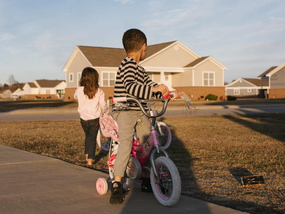Zwei Kinder draußen spielend mit Rad.