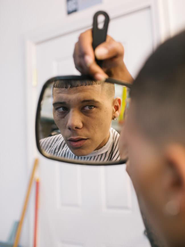 Junger Mann, der sich im Spiegel ansieht.