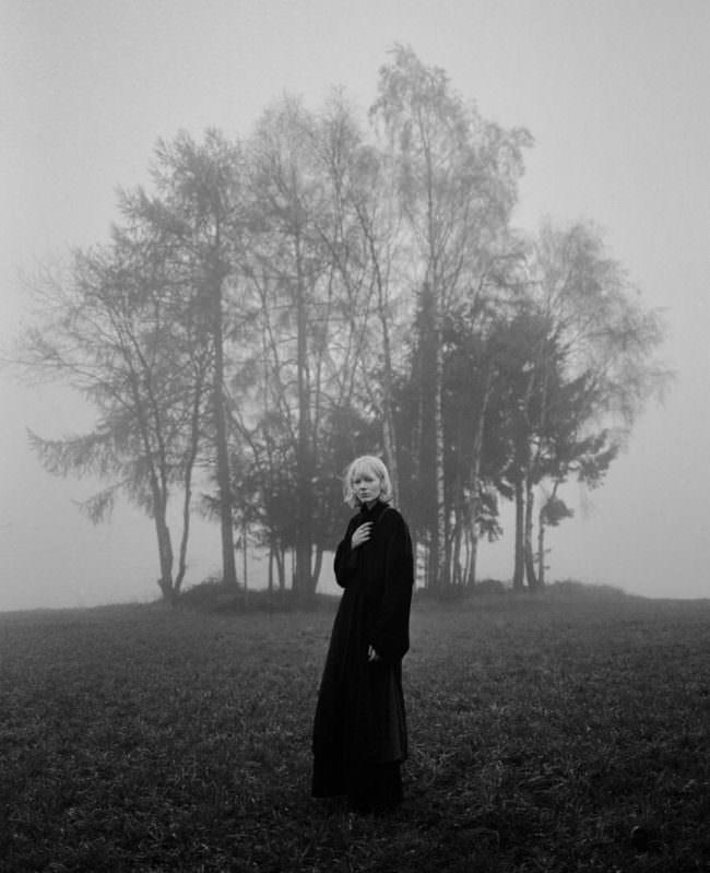 Frau im Nebel vor Bäumen