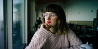 Frau mit Brille und Wollpulli