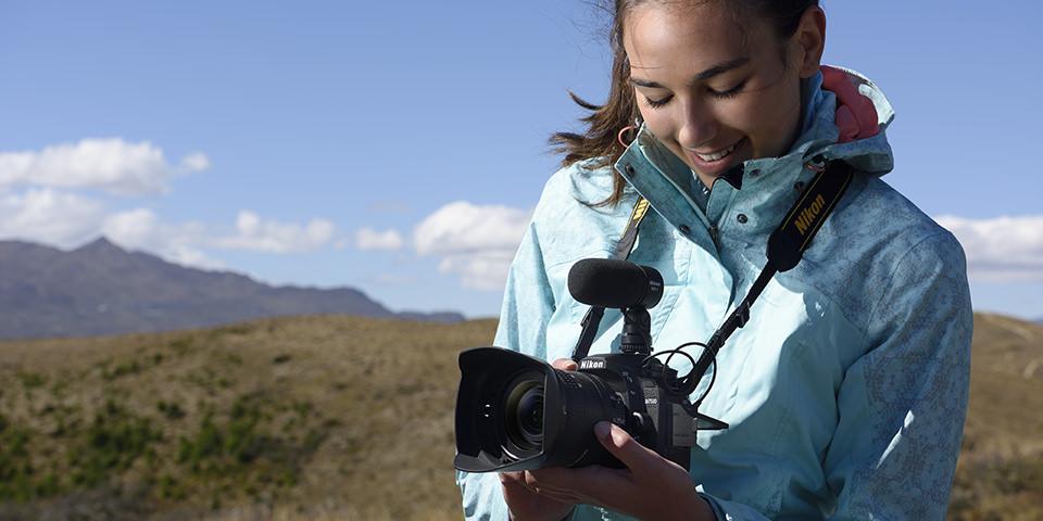 Frau mit Kamera in Landschaft