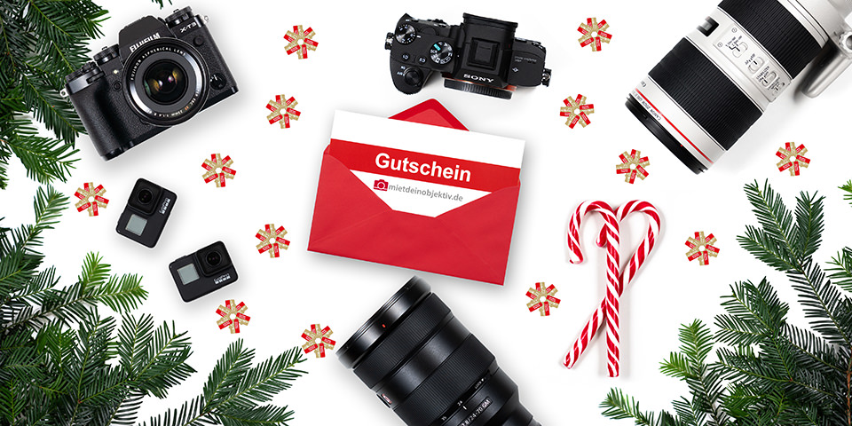 Kamerazubehör und Gutscheinumschlag mit weihnachtlicher Dekoration