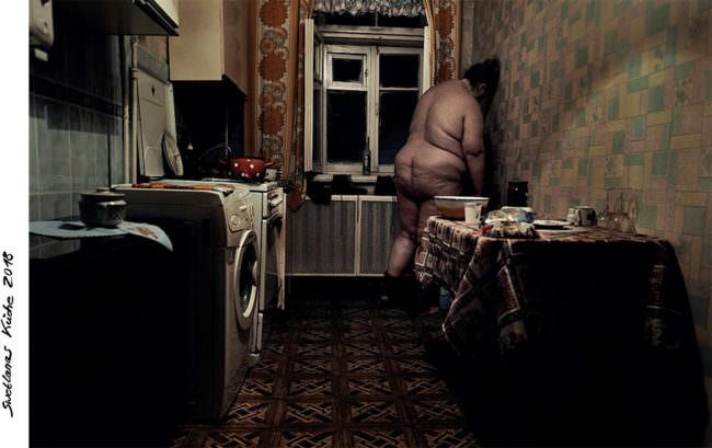 Eine nackte Frau lehnt an einer Küchenwand