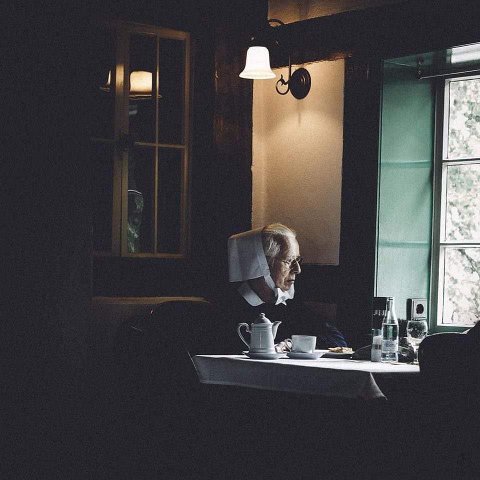 Nonne an einem Tisch vor einem Fenster