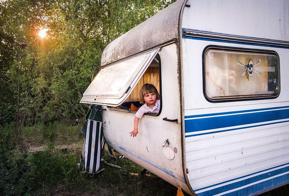 Kind lehnt sich aus dem Rückfenster eines Wohnwagens