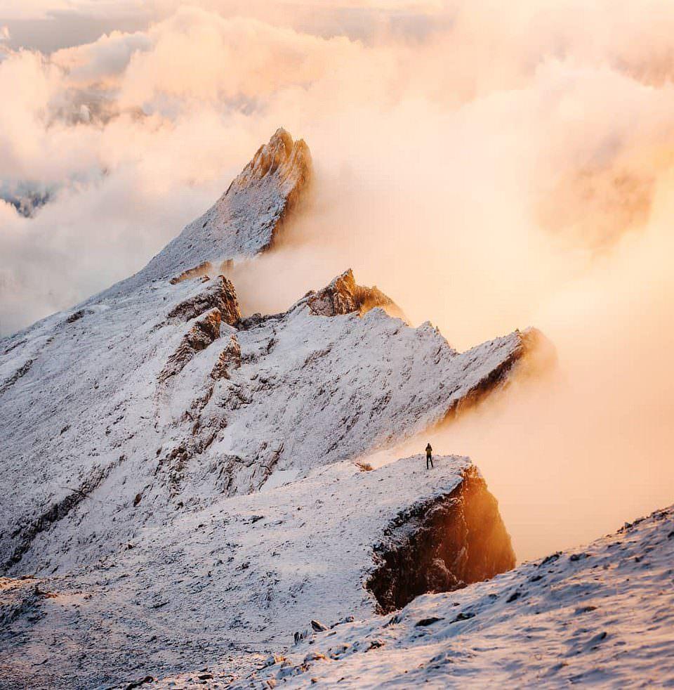 Person auf schneebedeckten Bergen über den Wolken