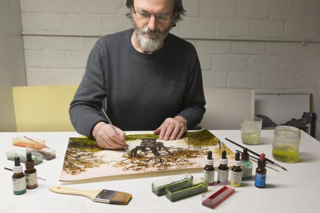 Mann beim Kolorieren einer Fotografie