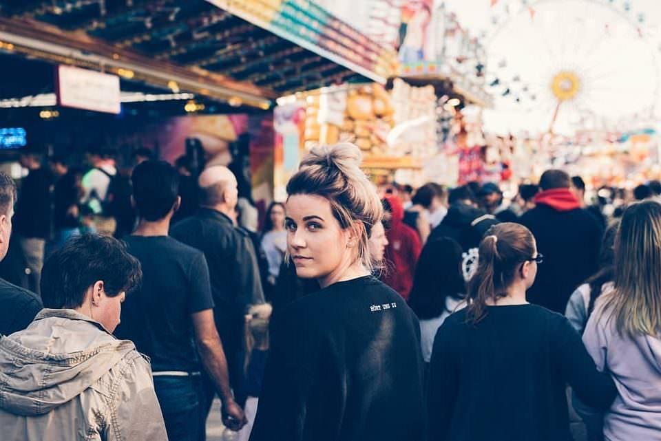 Frau dreht sich in einer Menschenmenge um