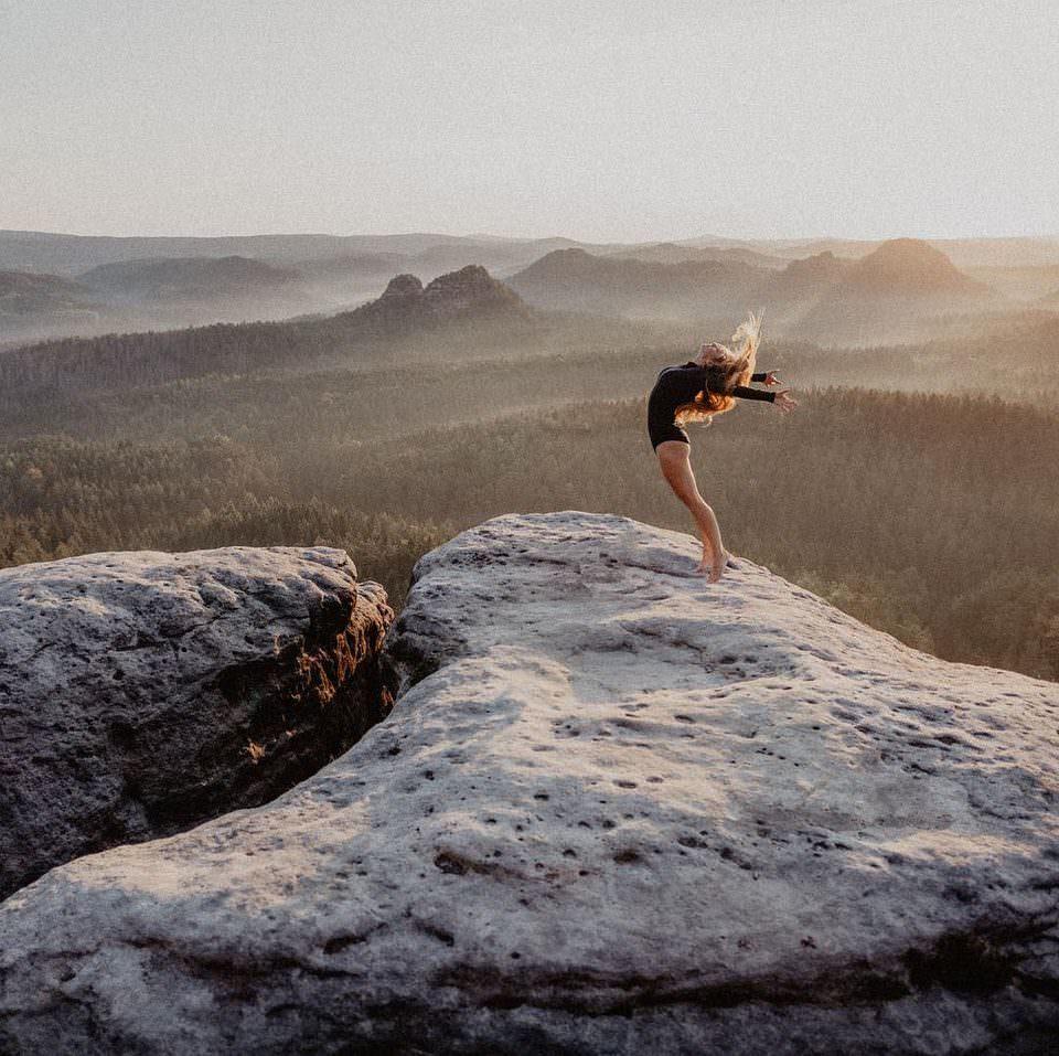 Frau auf einem Berg vor weiter Landschaft