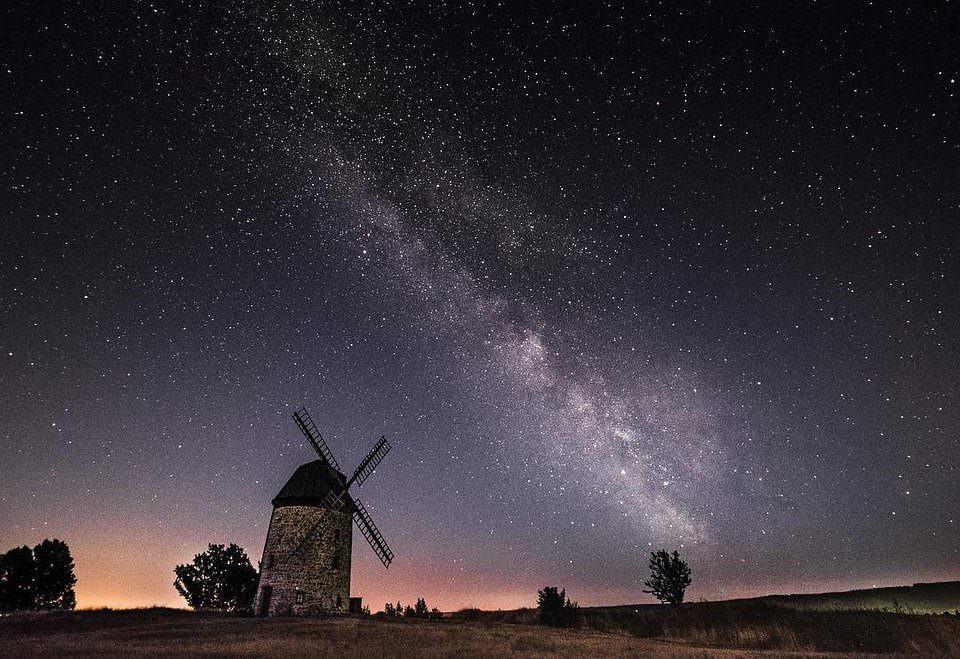 Nachthimmel mit Milchstraße über einer Windmühle