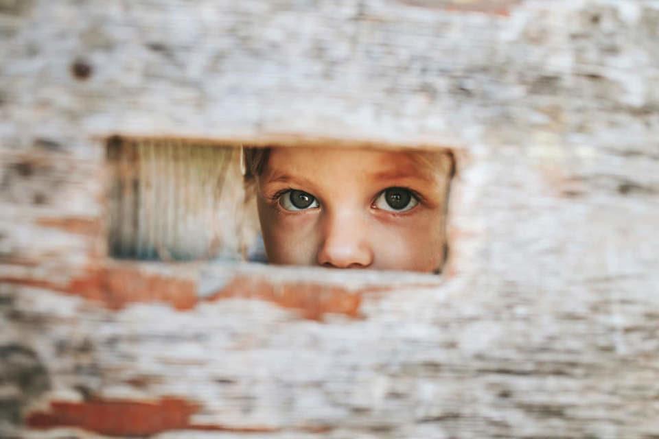 Kind schaut durch einen Spalt