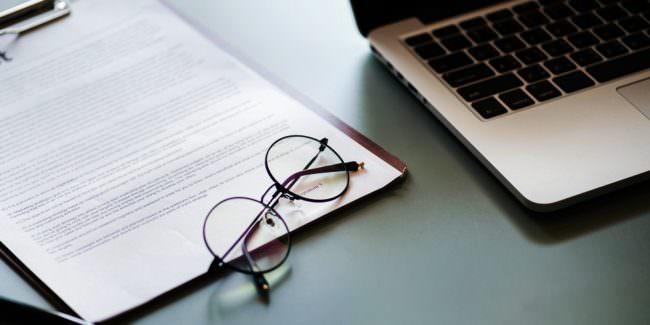 Schriftstück und Brille neben Laptop