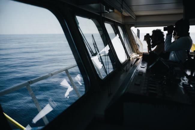 Männer auf einem Schiff mit Ferngläsern