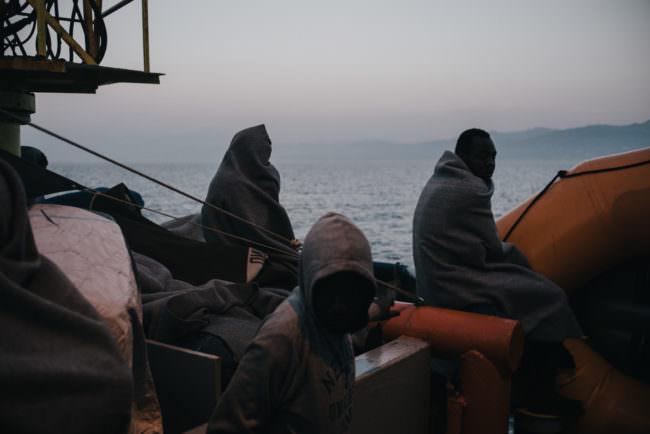 Menschen auf einem boot in Decken gehüllt