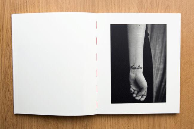Aufgeschlagenes Buch mit Bild eines Armes mit Ritzungen