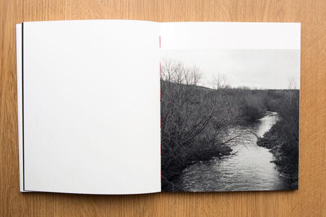 Aufgeschlagenes Buch mit schwarzweißer Landschaft mit Fluss