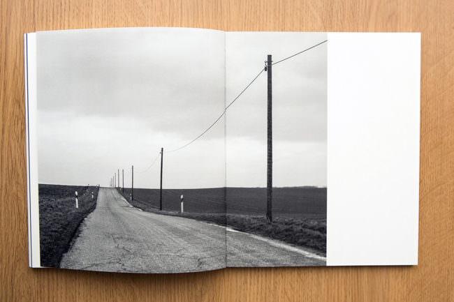 Aufgeschlagenes Buch mit schwarzweißer Landschaft mit Straße
