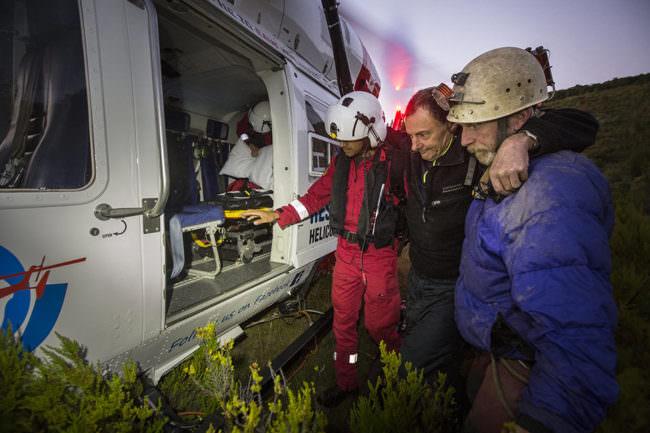 Zwei Personen stützen eine Dritte an einem Rettungshubschrauber