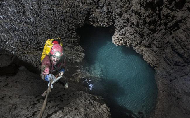 Kletterer in Höhle mit See.