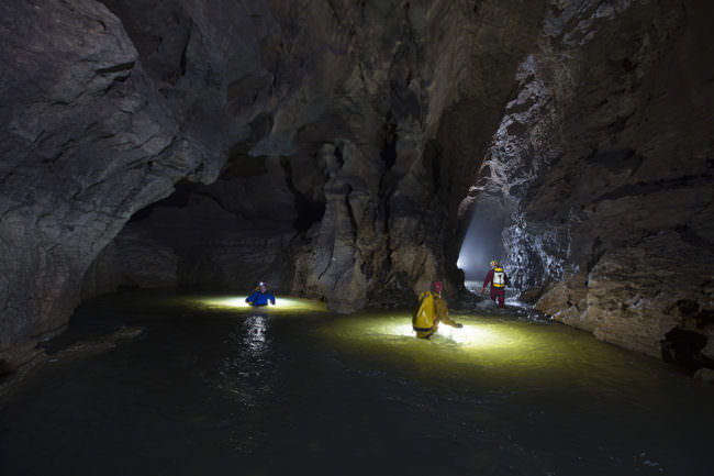 Personen gehen durch unterirdischen Fluss in einer Höhle