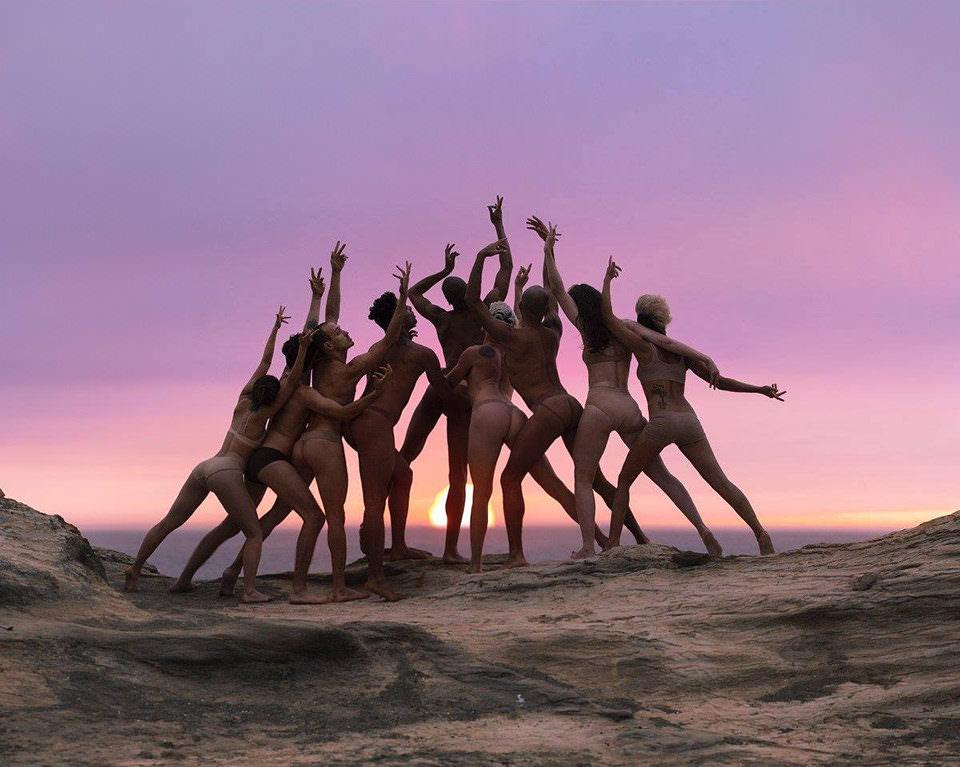 Menschen posieren vor einem Sonnenuntergang