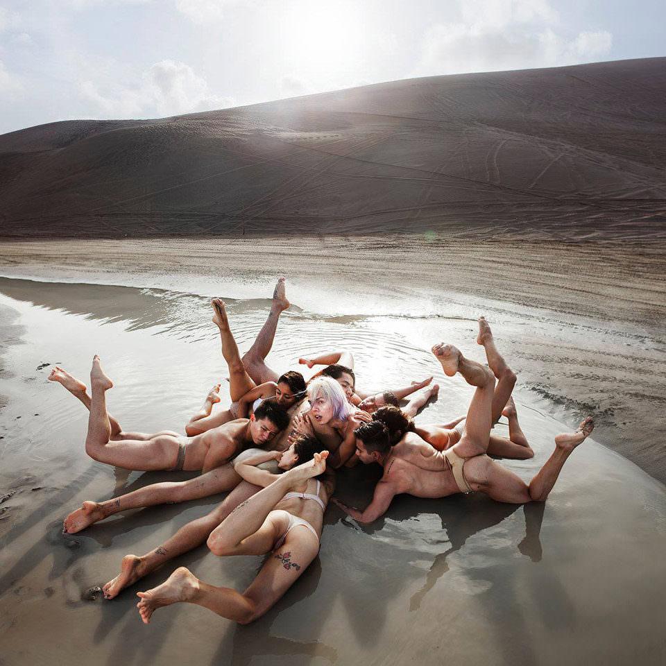 Menschen liegen in Formation an Strand