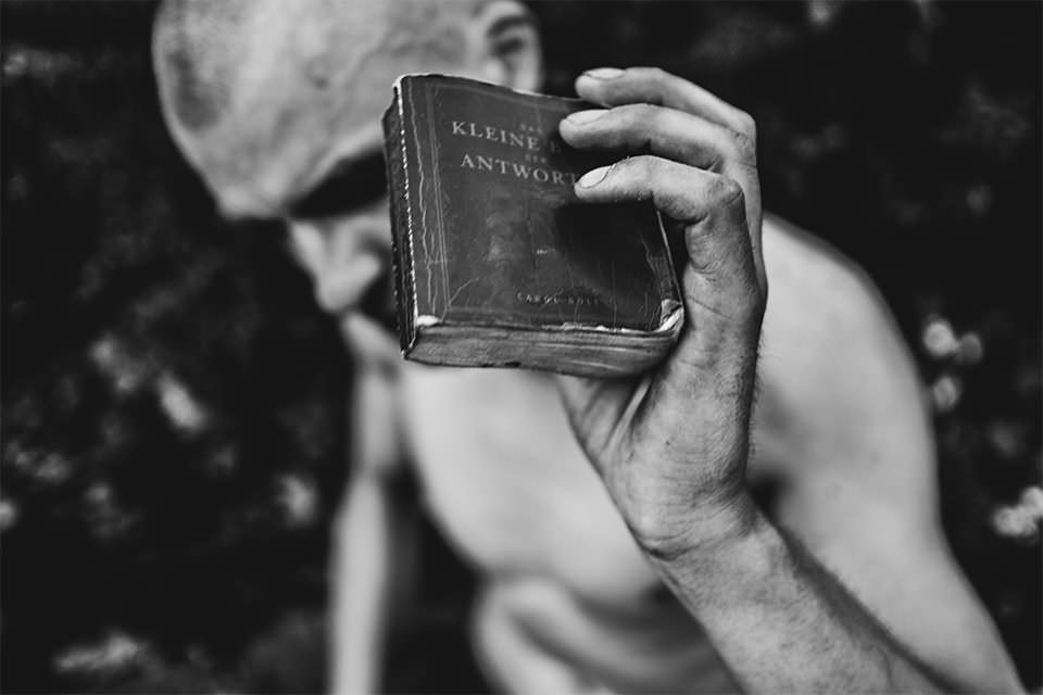 Mann hält ein kleines Buch