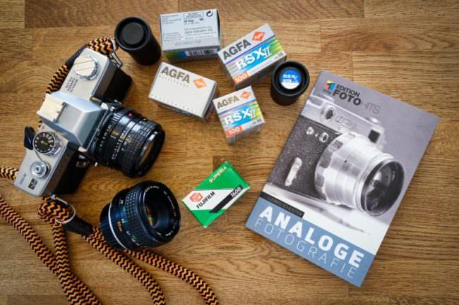 Buch, Kamera und Filme auf einem Tisch