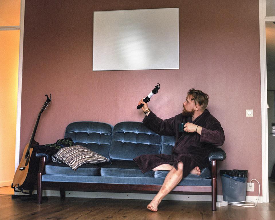 Mann sitzt auf Sofa im Bademantel