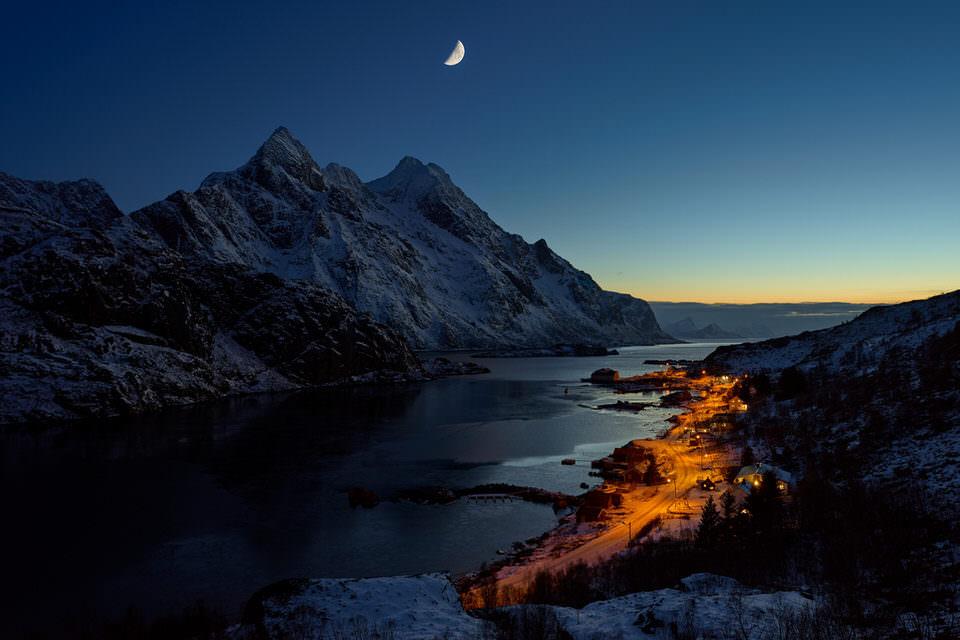 beleuchtete Stadt am Rande von schneebedeckten Bergen