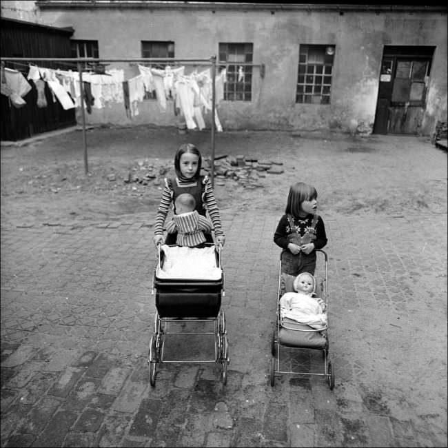 Zwei Kinder mit Puppenwagen vor einem Haus.