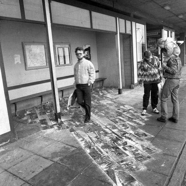 Personen an Haltestelle laufen oder schauen auf Bilder am Boden.