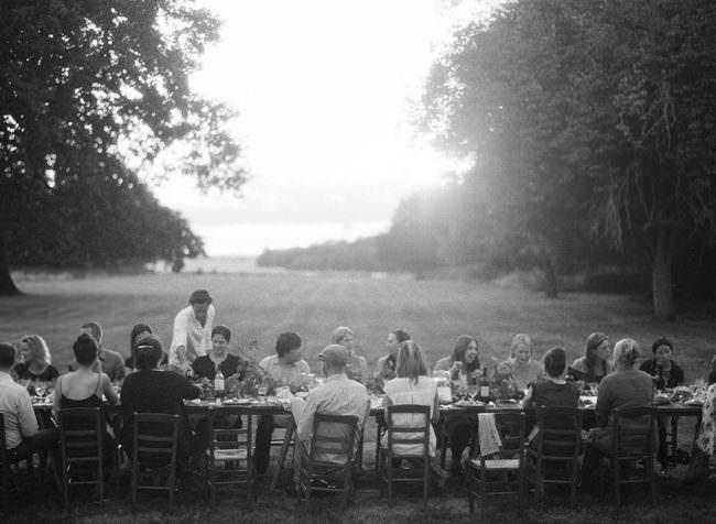 Hochzeitsgesellschaft isst draußen an einem Tisch