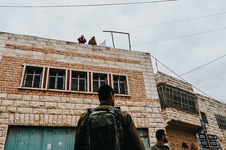 Menschen auf einem Hausdach sehen hinunter zu Soldaten