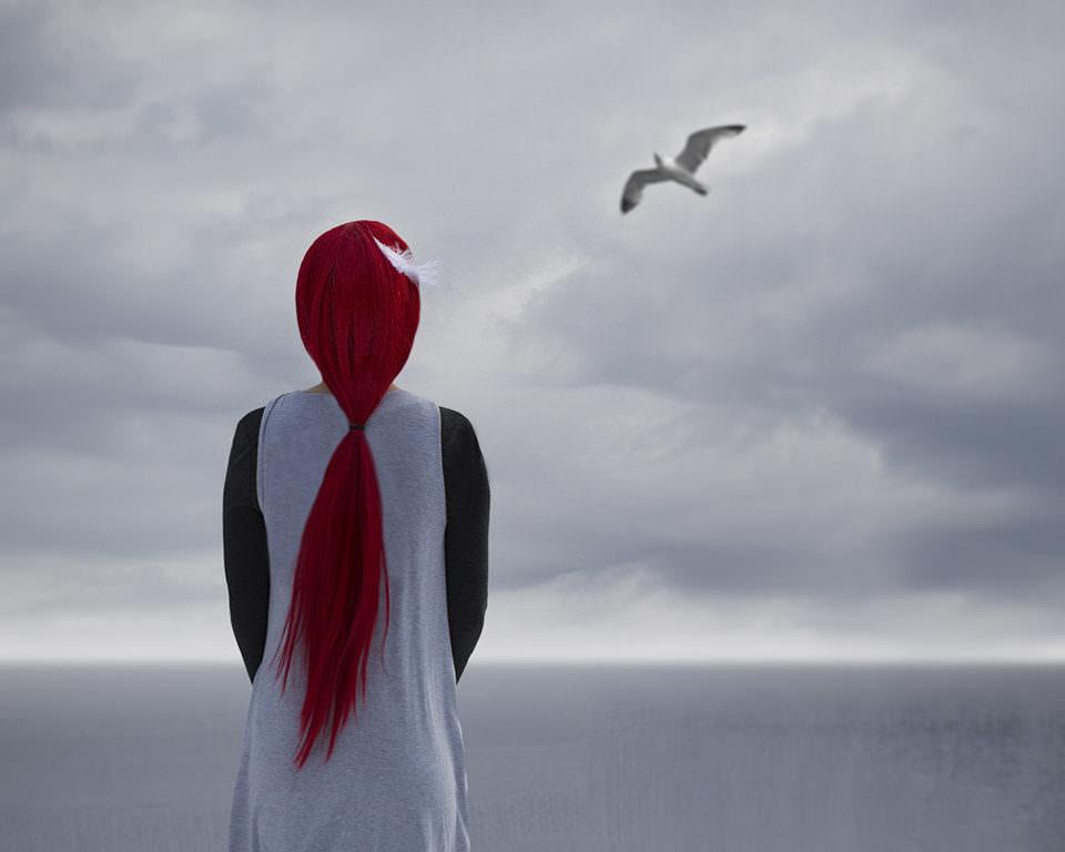 Mädchen mit roten Haaren sieht in die Ferne