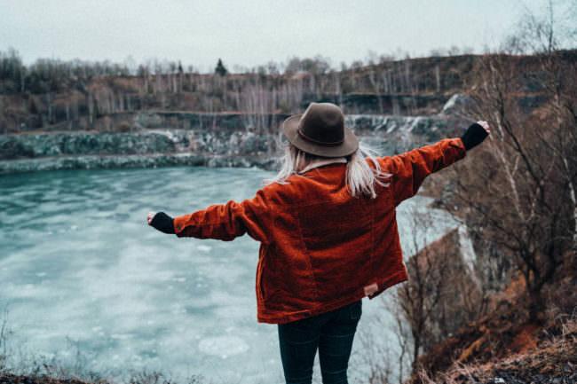 Frau sieht zu einem zugefrohrenen See