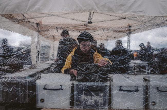 Flohmarktbesucher durch eine Plane fotografiert