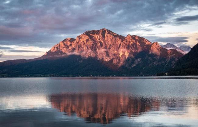 Ein Berg spiegelt sich in einem Gewässer