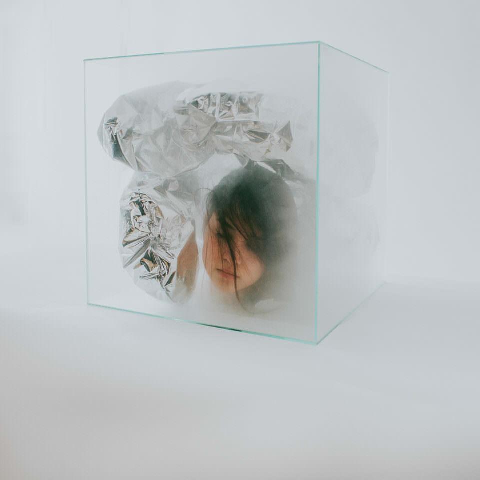 Frau mit Kopf in einer Glasbox und Folie