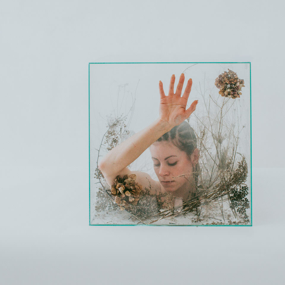 Frau mit Kopf in einer Glasbox und Pflanzen