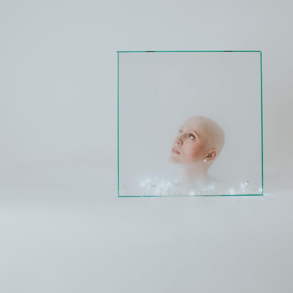 Frau mit Kopf in einer Glasbox mit Lichterkette
