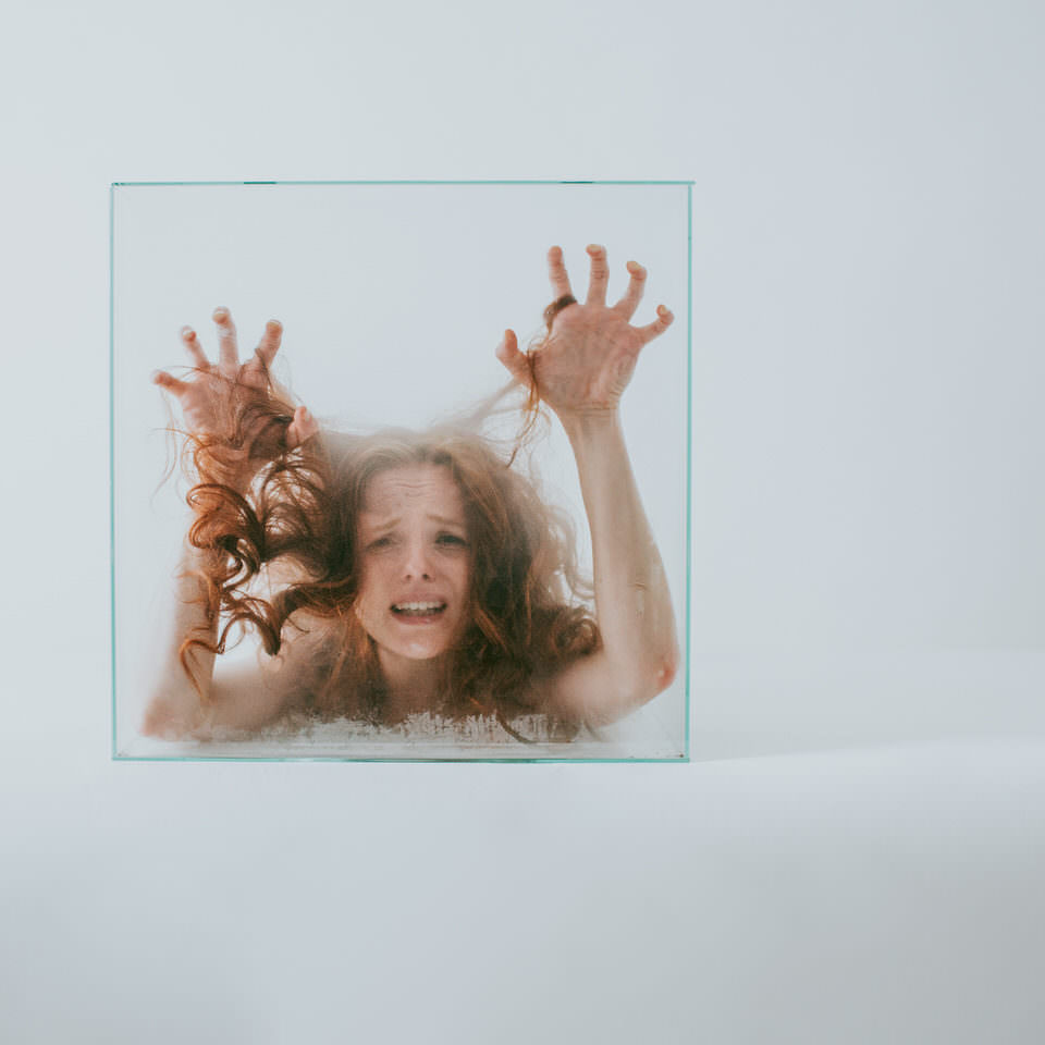 Verzweifelte Frau mit Kopf in einer Glasbox