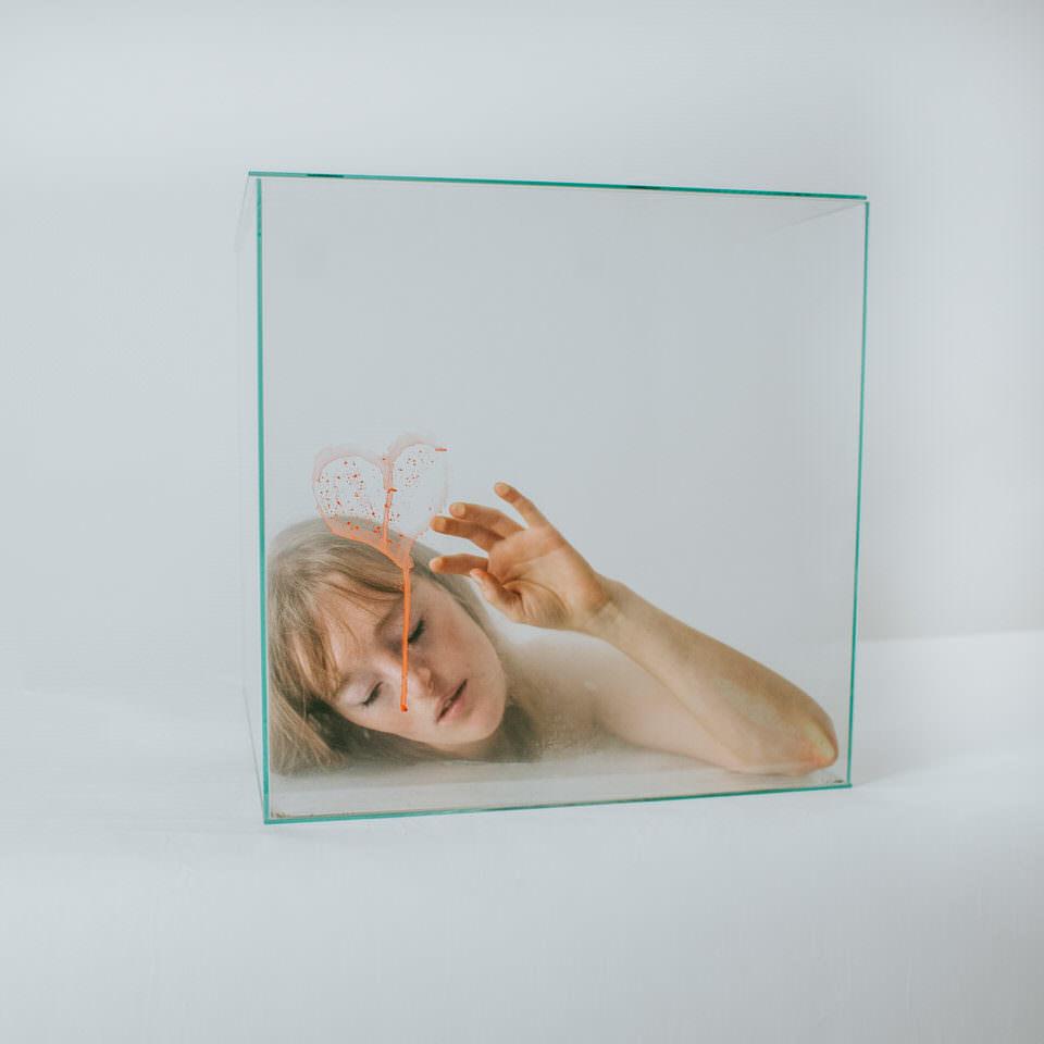 Frau mit Kopf in einer Glasbox malt ein Herz