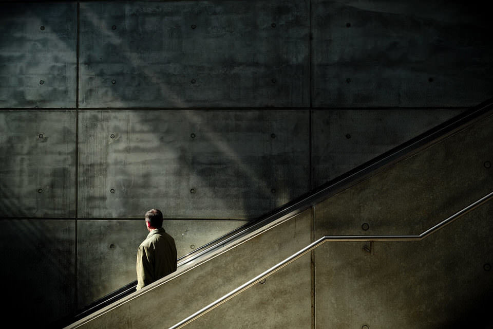 Mann auf einer Treppe vor einer Betonwand